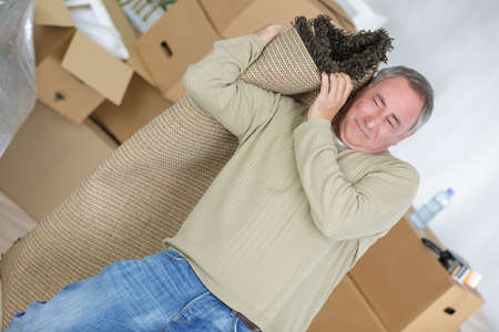 concealment: man carrying rolled carpet in living room Stock Photo