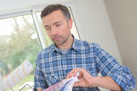 pent: man choosing paint color and pent paper