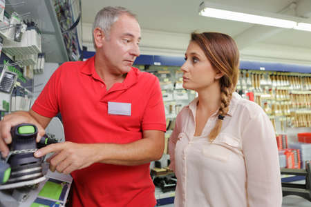 experienced positive seller offering working tooling in household store Stock Photo
