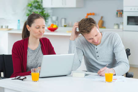 indecisive: indecisive couple looking at laptop at home Stock Photo