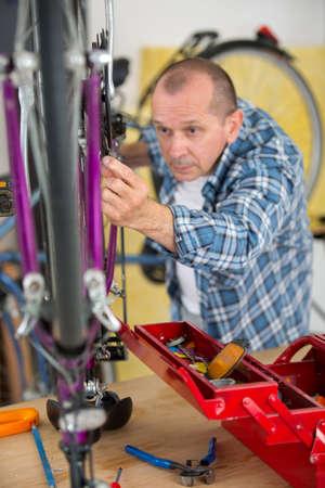 mechanic serviceman adjusting bicycle gear on wheel in workshop