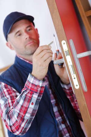 man fixing the door with screwdriver
