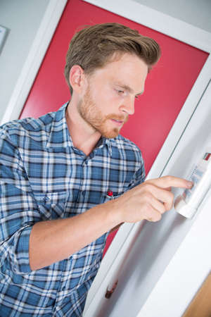 man adjusting temperature of electric boiler Stock Photo