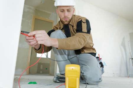 technician using a digital multimeter measuring voltage of a socket