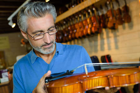 positive middle age man purchasing traditional violins in store