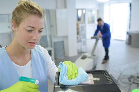 female cleaner cleaning corridor of business building Standard-Bild