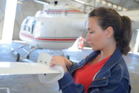 helicopter in the hangar and female engineer working