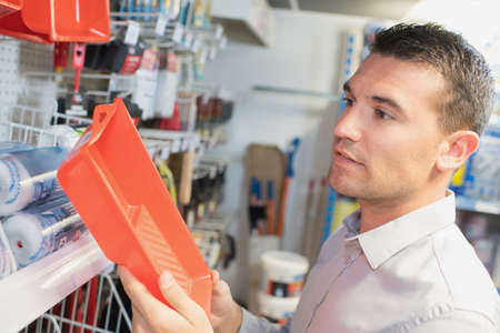 paintcan: worker or customer checking paint tray at hardware store Stock Photo