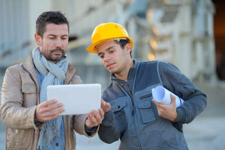 constructor and manager working on modern tablet outside renovated factory Stock Photo - 79675418