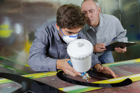worker and apprentice learning to spray painting Stock Photo