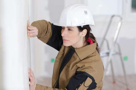 builder female indoor worker plastering wall with spatula trowel tool