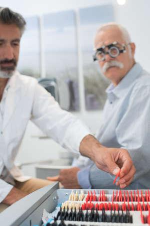 optician in surgery giving man eye test