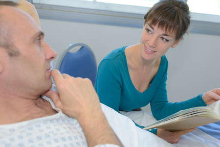 sickbed: smiling woman visiting his dad in a hospital bed Stock Photo