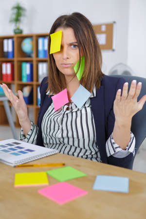 attractive businesswoman at office with post it on her forehead