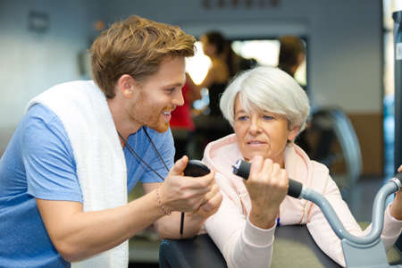 trainer encouraging senior woman exercising