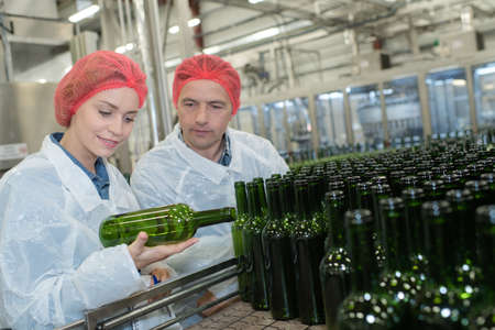 gallons: workers in factory checking robotic line for water bottling