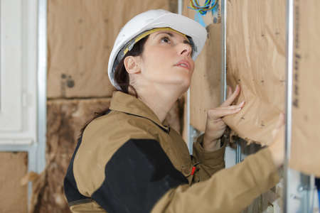 plasterer: female plasterer worker at a indoors wall insulation works Stock Photo