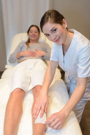 beautician doing depilation to woman legs with wax strip