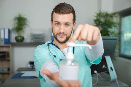 bactericidal: doctor holding pump dispenser of antibacterial handwash