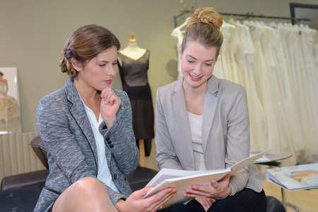 designate: designer and customer working in dressmaking studio Stock Photo