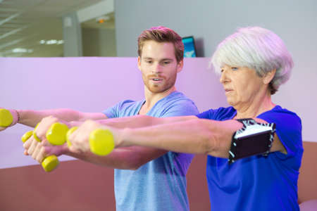 senior woman with instructor holding dumbbells in outstretched arms