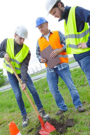 arando: Trabajadores físicos con pala y casco de seguridad