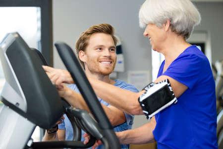 cardiovascular exercising: instructor aiding senior woman in gym Stock Photo
