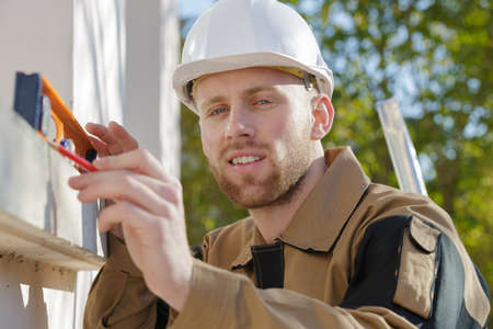 handyman standing outside with level Stock Photo