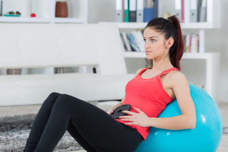 brunette using exercise ball at home in the living room