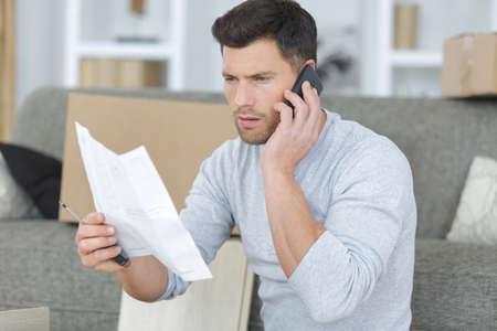 Uomo che utilizza il telefono mentre montano scaffale a casa Archivio Fotografico - 80065299