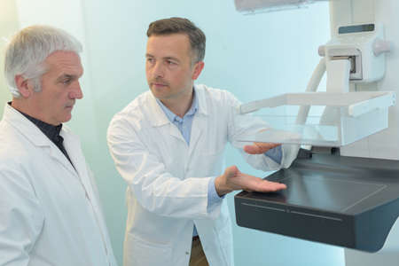 ultra modern: doctor explaining another doctor how the new xray machine works