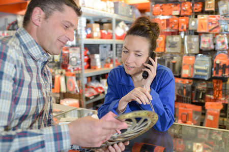 couching: salesman showing tools to female customer in hardware shop Stock Photo