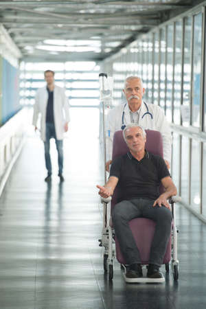 long term: doctor looking at senior patient on wheel chair Stock Photo