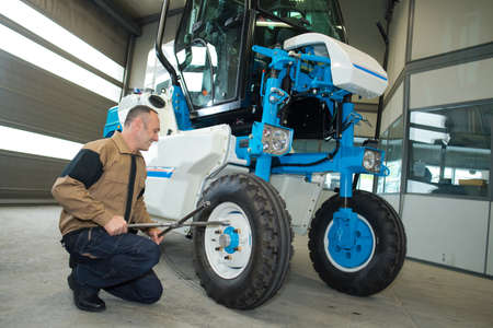 man fixing a tractor in an agro-industrial hardware Stok Fotoğraf - 80063649