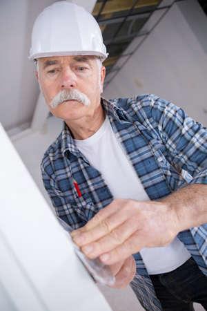 plasterer at indoor wall renovation decoration with palette knife