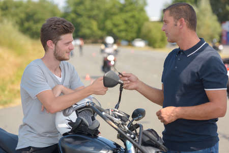 Man taking motorcycle training course talking to instructor