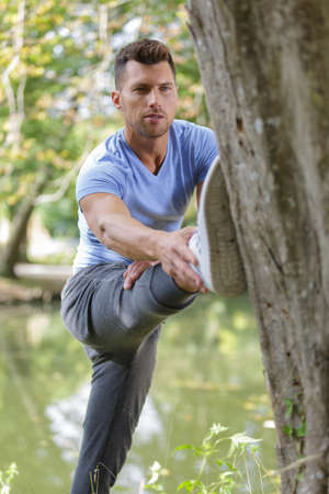 Man stretching out his leg against a tree