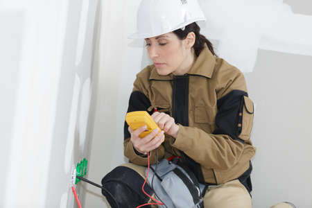 female technician measuring voltage of a socket