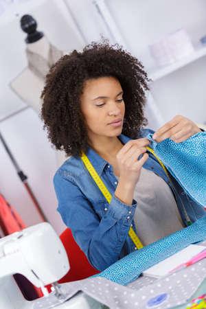 Young seamstress hemming material