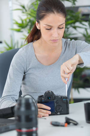 dismantle: Woman working on camera Stock Photo