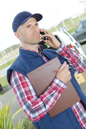 koncentrovaný: Man holding clipboard and talking on telephone