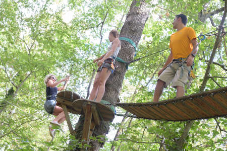 fearful: Adults on rope bridge between trees