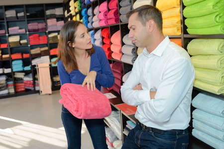 Couple discussing color of towel to buy