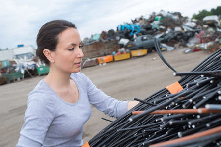 Woman in scrapyard stacking cables Stock Photo