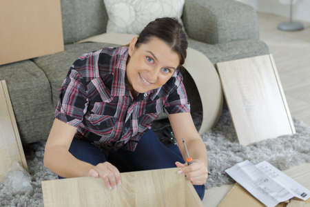 luxury apartment: happy girl assembling a new furniture