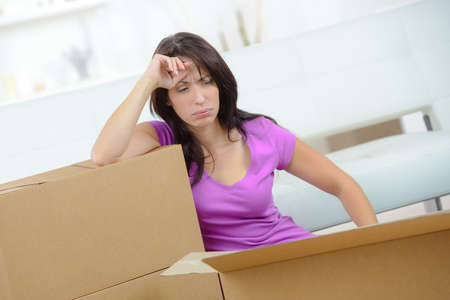 amongst: Depressed woman amongst packaging boxes Stock Photo