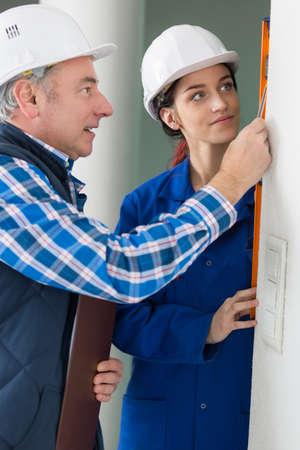 aligned: Builders using spirit level on vertical wall