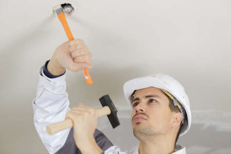 man is hammering the ceiling