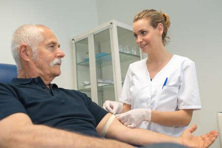 Nurse securing tourniquet to patients arm