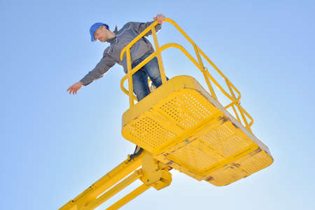 Man in cherry picker bucket pointing into distance Stock Photo
